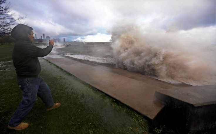 Manuel Hernandez takes video of high waves crashing into a break wall on the south shore of Lake Mic... - AP Photo/M. Spencer Green