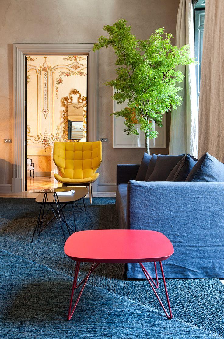 Amplio espacio presidido por una gran alfombra que cubre casi toda la superficie del suelo y donde se encuentran sofás de color azul oscuro y butacas de tela tapizadas en amarillo y con estructura de madera, también dos mesas auxiliares de distinto tamaño lacadas en brillo.