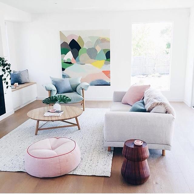 modern living room with pink and pastel tones, white walls, round coffee table