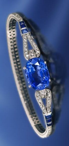 An art deco sapphire and diamond bracelet, Cartier, French, circa 1925 centering a cushion-cut sapphire, joining a slender looped line of old European and single-cut diamonds, accentuated by calibré-cut sapphires; signed Cartier Paris London New York, no. 4262, with French assay mark and maker's mark for Renault, within original fitted box; sapphire weighing approximately: 17.20 carats; estimated total diamond weight: 2.60 carats; mounted in platinum.