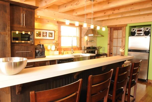 """Armoires de cuisine de style classique avec une touche de champêtre. L'îlot et la totalité de la cuisine ont été réalisé en merisier. Les portes rainurées apportent une touche champêtre à la cuisine.  Le tout est harmonisé avec un comptoir de stratifié carré de 2"""" d'épaisseur."""