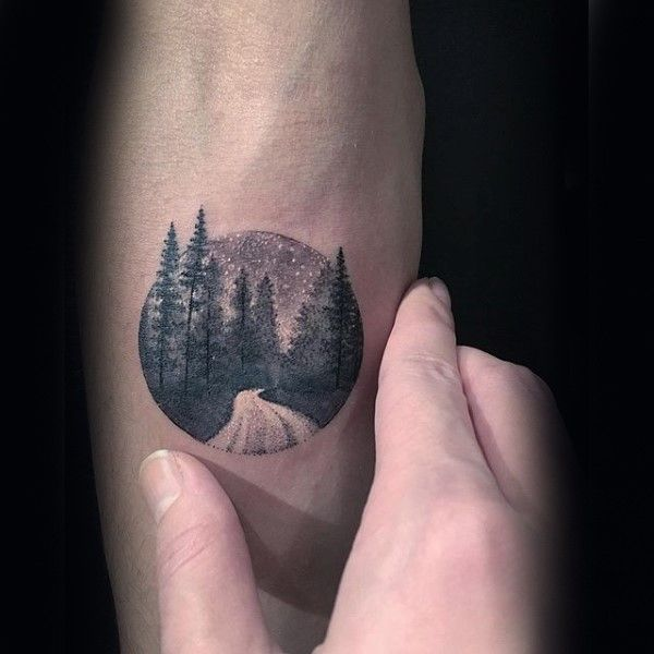 Small circle shaped stippling style tattoo of night forest road