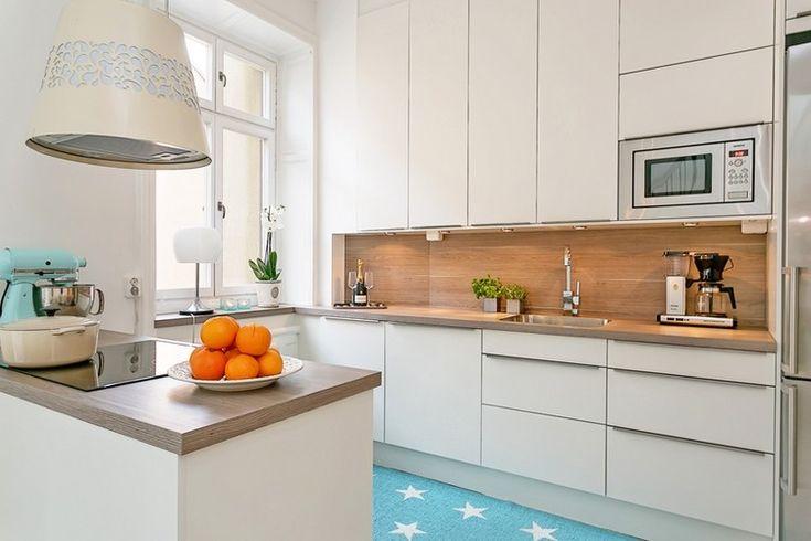 weiße Küche mit kleiner Insel in weiß und holz