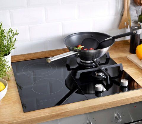 Um grande plano de um wok cheio de legumes, ao lume num bico de uma placa IKEA, com zonas de indução e a gás.