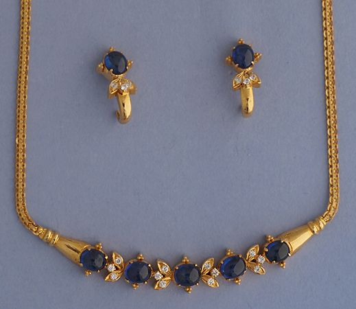 Diamond & Blue Sapphire set This 21k Gold necklace & earrings set is ahead of its time. Length of the necklace is 16 inches. The set is studded with Total Weight of diamonds is 0.55 carats & 15 carats of blue sapphires. The J shaped earrings curve below the ear. #21k, #21k Gold, #21k Gold set, #diamond, #blue sapphire, #necklace, #earrings, #tops, #diamond tops, #bismarck, #chain,