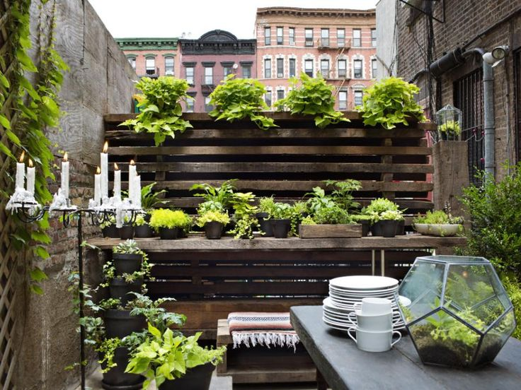 Urban living often means cramped quarters both indoors and out so make the most of the space you have by thinking vertically. Designer Dan Faires repurposed wood beams from a NYC building that was slated for demolition to create this privacy wall with shelves he filled with potted plants. See more of Dan's NYC digs.