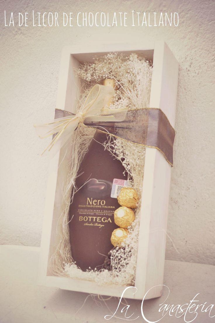 La de Licor de Chocolate Italianoes un arreglo corporativo muy original perfecto para Navidad con una lujosa botella de Licor de Chocolate y Ferrero Rocher en una cama de flores secas y cálidos ac…