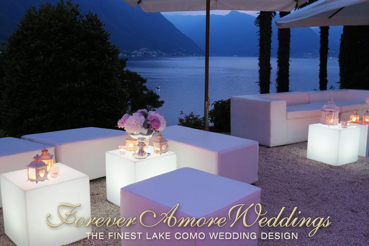 Evening feel of wedding reception Lake Como, Villa Balbianello, Terrace Loggia Segré. White ecoleather lounges and luminous side tables. Picture by ForeverAmoreWeddings ©