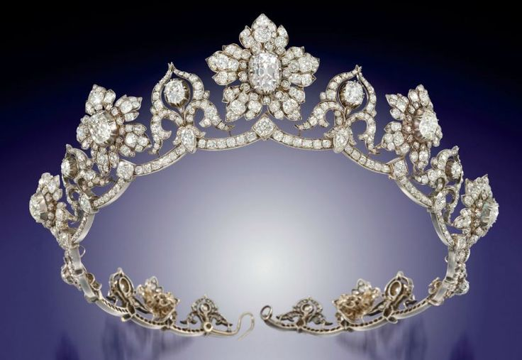 Circa 1850 DIAMOND TIARA: a series of nine old-cut diamond graduating flower head clusters centerd by old-cut pear and cushion shape diamond collet highlights, the central principal very light pink diamond weighing approximately 6.17 carats, interspersed by ten similarly-set stylized cusp motifs of ribbon scroll design, raised on an undulating diamond line frame, mounted in silver and gold; each flower head cluster detachable to form a brooch.
