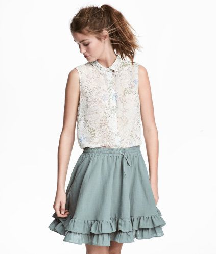 Natural white/floral. Sleeveless blouse in airy chiffon with a collar and buttons at front. Rounded hem, slightly longer at back.