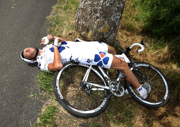 Lilian Jegou of Francaise des Jeux lies on the road after crashing into a tree during the Tour de France in 2008