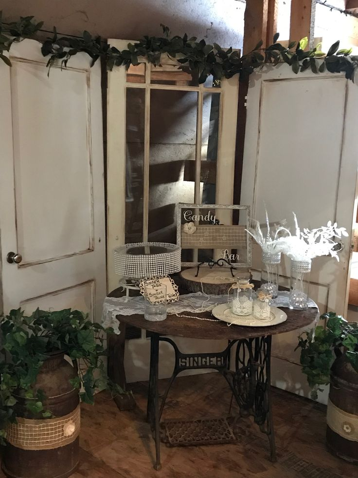 A shabby chic Cake or card Table with a old singer sewing machine stand, using the old doors for a elegant backdrop.
