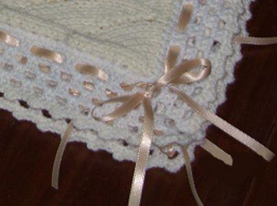 Schema e istruzioni per realizzare da sole una copertina fatta a maglia per il tuo bambino con rifiniture all'uncinetto