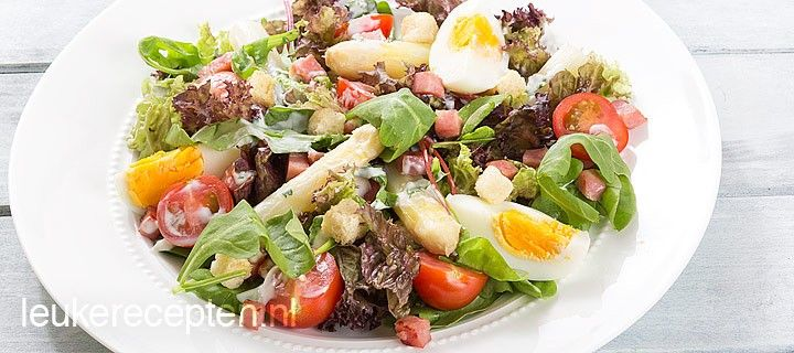 Lauwwarme maaltijdsalade met witte asperges, ei, hamblokjes en tomaatjes met een romige dressing