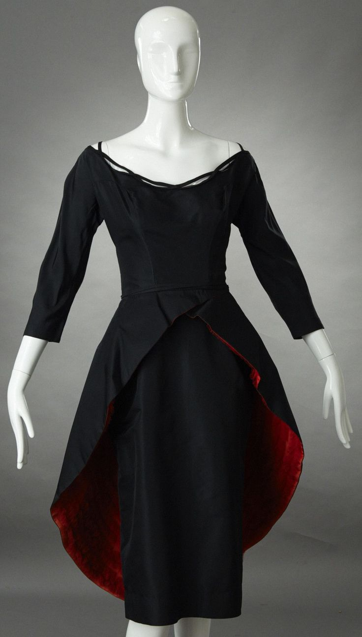 1950s Ceil Chapman black satin cocktail dress with matching black satin over skirt with rows of red tulle ruffles on the underside. The neckline, both front and back are scooped. The neckline is borde