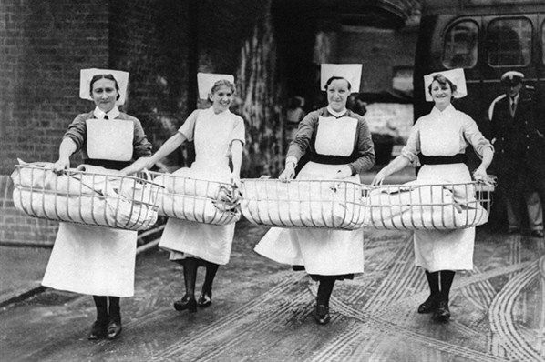 Nurses carry cribs containing newly-born babies from the maternity section of a hospital in south-east London, the morning after a German air raid left the building severely damaged.