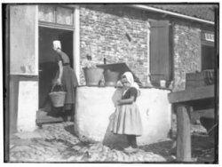 1916 Boerenerf aan de Duinweg in Zoutelande Het meisje Liesbeth in klederdracht bij de waterput van de boerderij met op de achtergrond, gezien op de rug, een vrouw met een emmer in de hand, die de boerderij binnengaat.