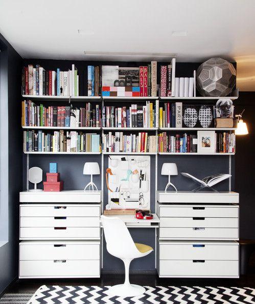 Bradford Shellhammer's collection of books on white shelves. Lonny June 2013