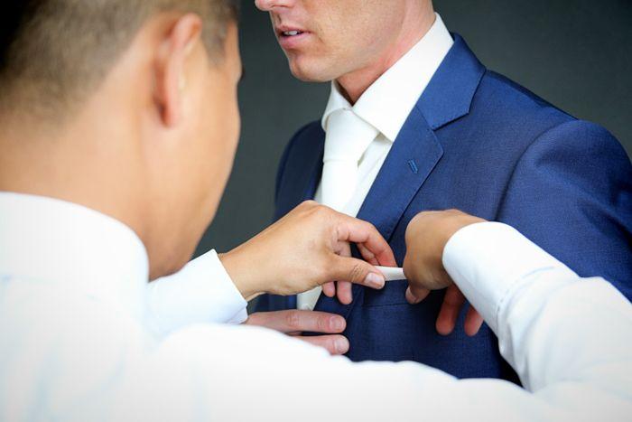 pochet wordt goedgedaan bij de bruidegom