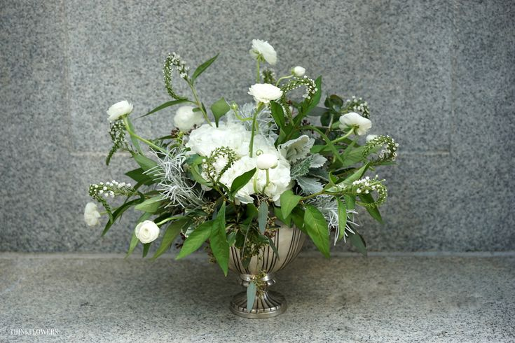 White ranunculus, veronica, white hydrangea, dusty miller and eucalyptus in a…