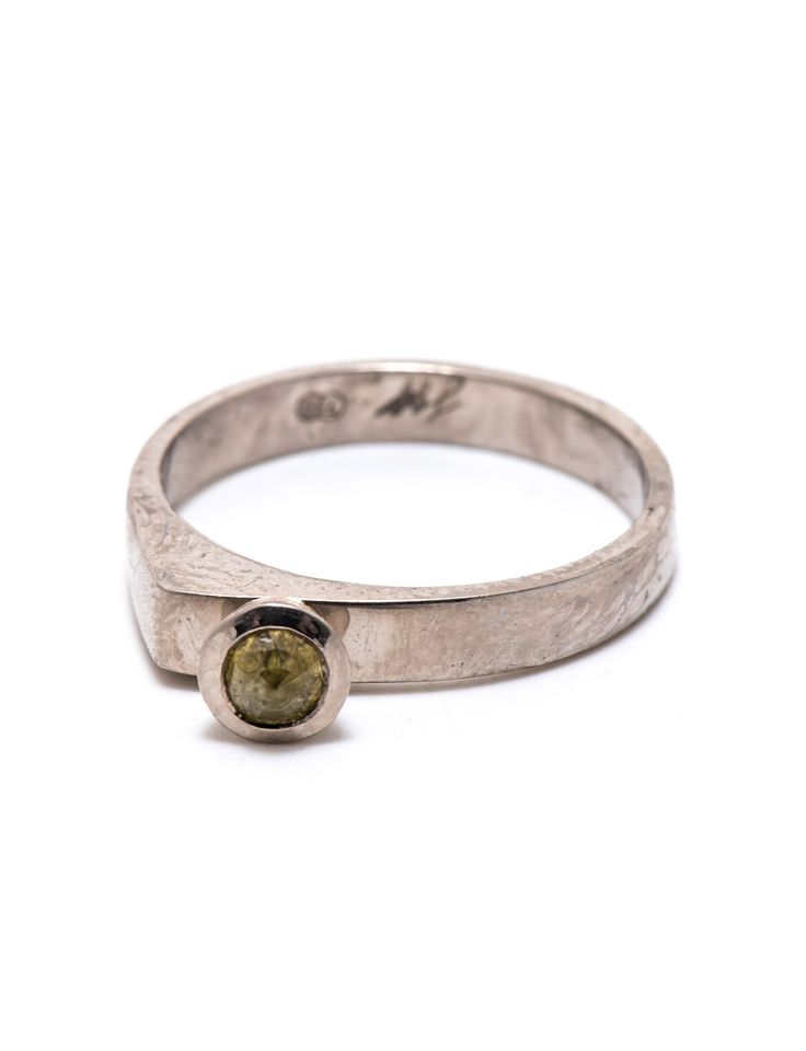 A rose cut yellow-green diamond perches asymmetrically on a white gold knife edge ring by Sarah Heyward. Browse unique wedding and engagement rings.