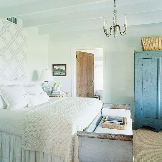 A checkered quilt, used as a ceiling-high headboard, introduces instant vintage appeal to this master bedroom. The soft blue of the pattern in the quilt is echoed by chalky milk paint on a primitive armoire and a distressed finish on a curvaceous antique Swedish bench at the foot of the bed./