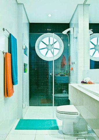 A janela deste banheiro projetado por Daniel Tesser é a esquadria redonda, que contrapõe às linhas retas dos demais elementos. Nichos na parede deixam os objetos de higiene à mão dos moradores, mas longe da vista das visitas. A parede ao fundo é revestida por pastilhas de tom azul-escuro.