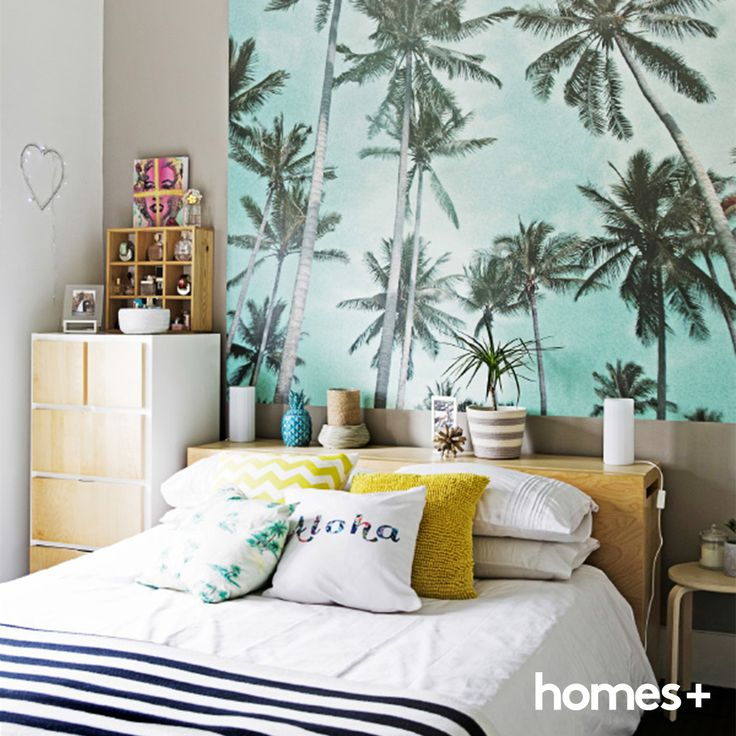 This #bedroom in Maree's #beachy #home has a #tropical #holidayfeel. #As featured in the March 2015 issue of homes+. #beachhouse #artwork #palmtrees #interior #bed #sidetable #pillows #cushions #vase #decor #colour #style #homesplusmag