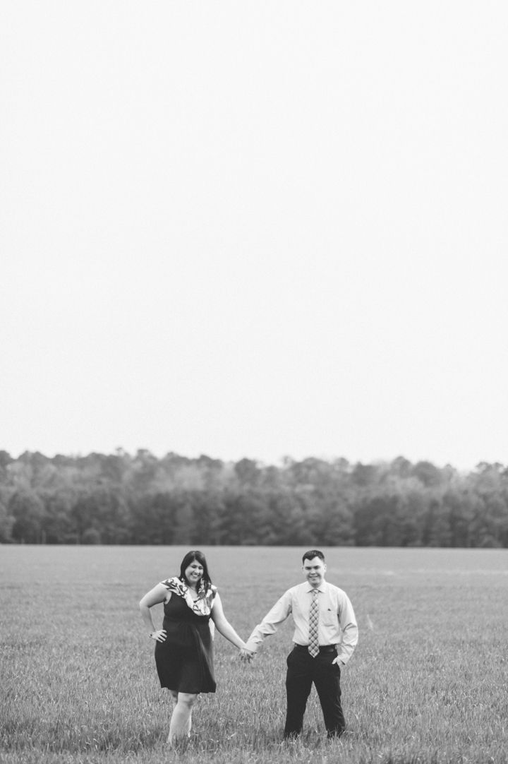 b/w photo of ami and michael standing in the field of grass at st. mary's city, MD - by Pearl Paper Studio