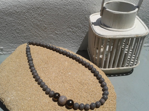 Uniquely styled long necklace with grey and metallic beads.