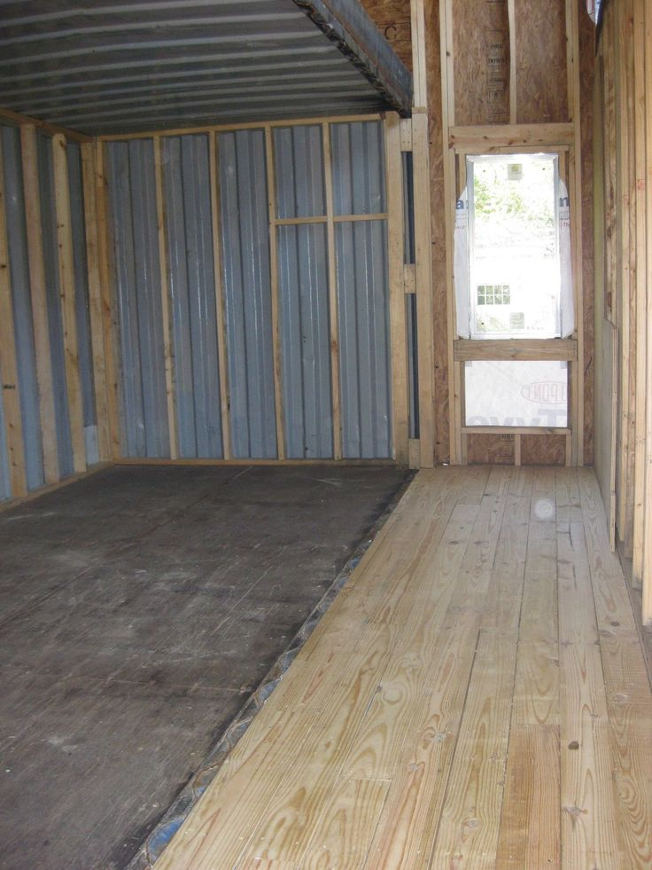 Interior construction of a shipping container, one side of the container has been removed to widen the room. To do this there must be a very strong beam added to support the containers roof. You can just see the beam in this image. Any structural changes like this should be approved by a structural engineer.
