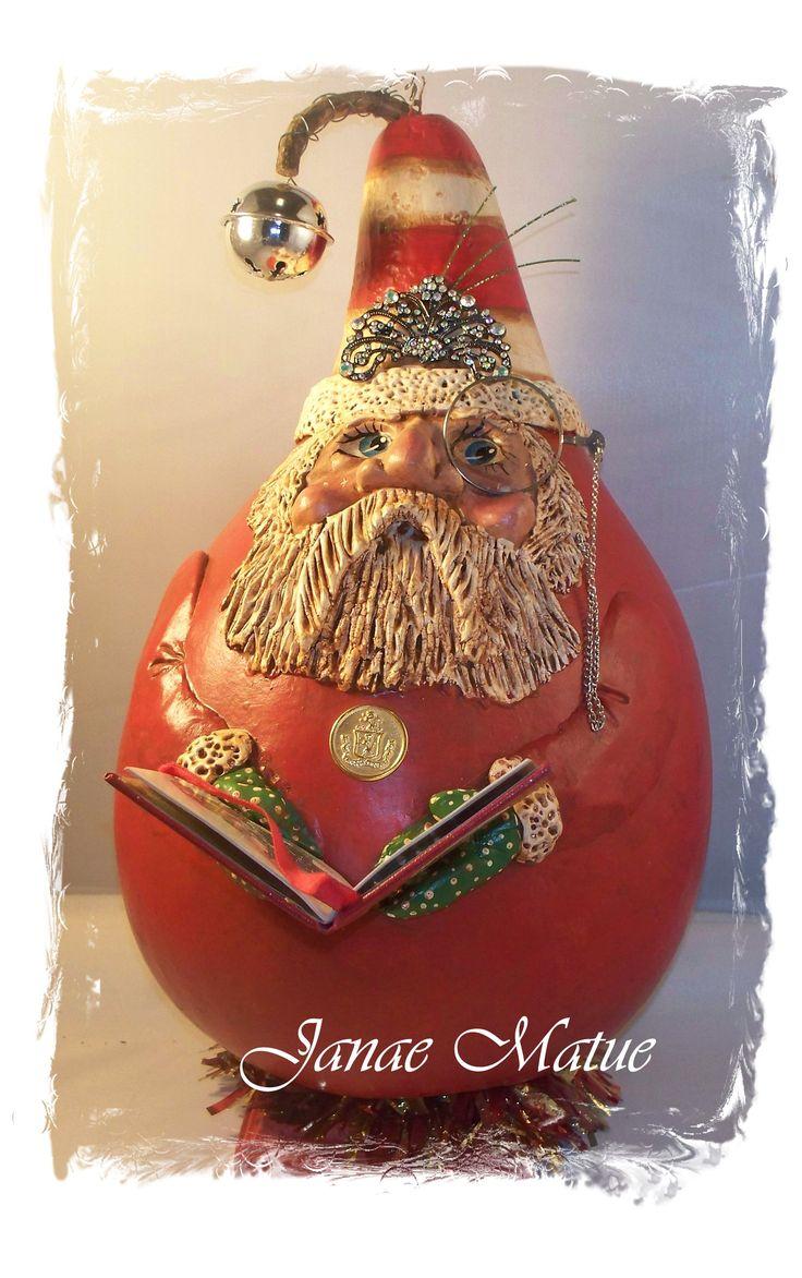 A sculpted gourd Santa holding a book