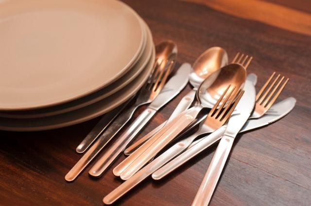 Loose cutlery and a stack of empty plates on a buffet table with knives, forks and spoons on a wooden tabletop - free stock photo from www.freeimages.co.uk