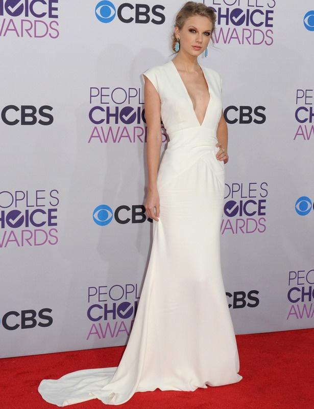 Taylor Swift se ha unido a la moda de lucir vestido blanco para la noche y lo demostró en los People's Choice Awards. Su diseño lo firma Ralph Lauren y nos gustó su corte con cola y pronunciado escote en pico sobre el que destacaban unos espectaculares pendientes azul turquesa de Sutra y anillo de Le Vian.
