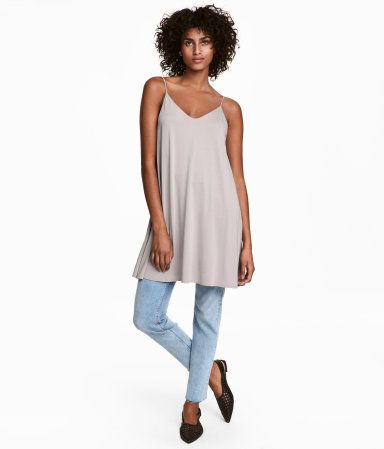 Light taupe. Short jersey dress. Narrow shoulder straps, V-neck at front and back, and double layers of fabric at top.