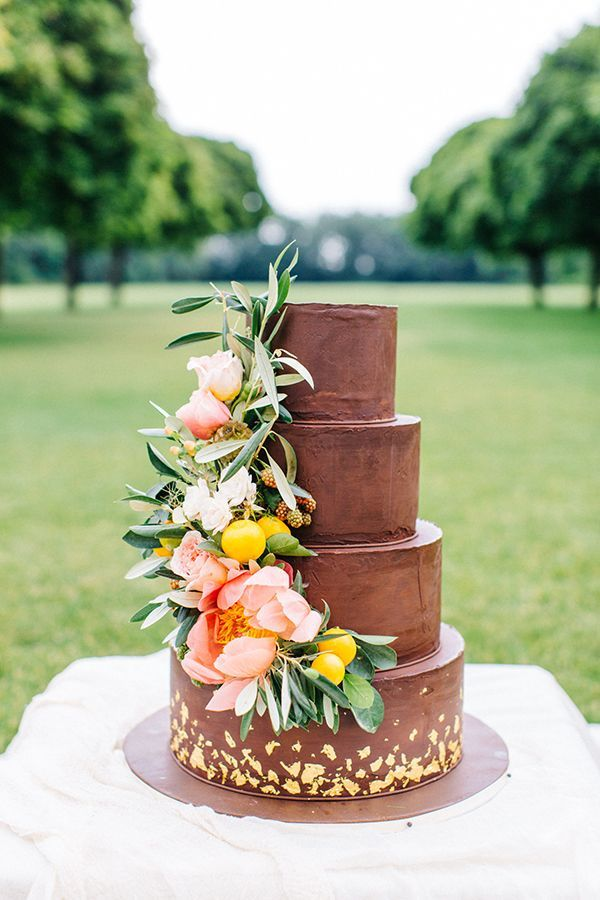 Made by Zola Auböck, the couple's four-tiered chocolate cake was flecked with gold leaf and brightened by a cascade of peonies, lemon branches, and unripe blackberries. | Photo by Tony Gigov