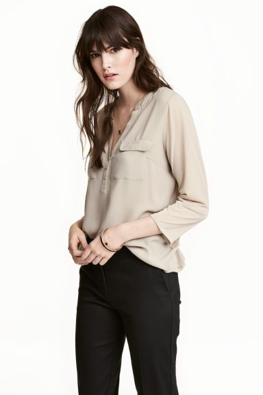 Crêpe blouse: V-neck blouse in a crêpe weave with a small stand-up collar, button placket, flap chest pockets and soft jersey 3/4-length sleeves. Slightly longer at the back.