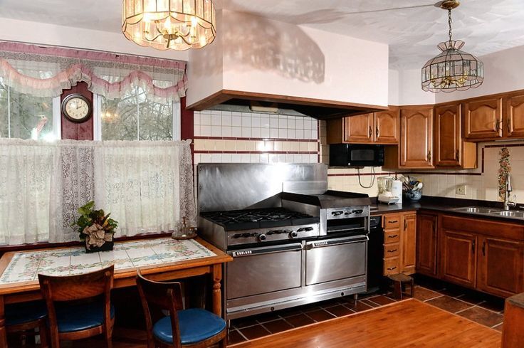 Kitchen in 200-year-old home.  The centerpiece of the room is the large commercial stove, which includes six burners, two ovens, a griddle and a broiler. The kitchen also has access to the back patio.