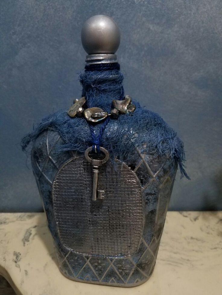 Chalk painted Crown Royal bottle with silver accent paint, blue gauze, key and abalone/beads from an old necklace