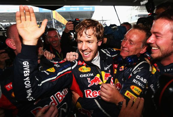 Sebastian Vettel of Germany and Red Bull Racing celebrates with team mates in his garage as he clinches the drivers world championship during the Brazilian Formula One Grand Prix
