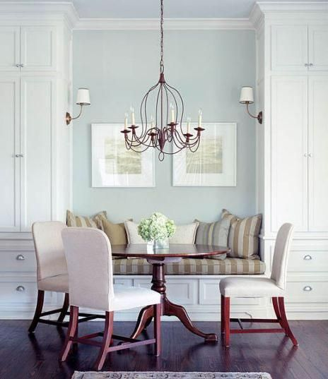 Love the soft blue gray paint wall color in this dining room space! Chandelier, sconces, photo gallery, built-in cabinets, round wood dining table, upholstered white cream dining chairs, built-in bench seating with striped upholstered fabric and brown, gray and cream throw pillows and espresso wood floors!...well said LOVE IT