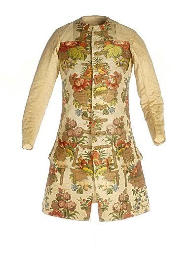 Chupa Rococó. (1730-1740) Chupa confeccionada con dos tipos de tejidos: los delanteros, de seda brocada y decoración floral espolinada, y las mangas y espalda, de seda labrada en su color natural. Ajustada al torso y con cuello a la caja. La manga, larga y con forma en el codo. En los faldones delanteros, bolsillos con grandes carteras decorada con ojales fingidos de galón de oro, idénticos a los que vemos en los delanteros. Hechura y tejido la sitúan cronológicamente entre 1730 y 1740.