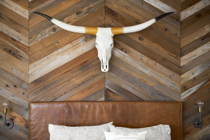Studio Revolution creates a warm and welcoming master suite from an oddly shaped loft. An eclectic mix of unexpected design details, like an Eames chair and floral wallpaper, turns this space into a fun, funky retreat, while a leather headboard and faux-cow skull give the room a slight Southwestern feel.