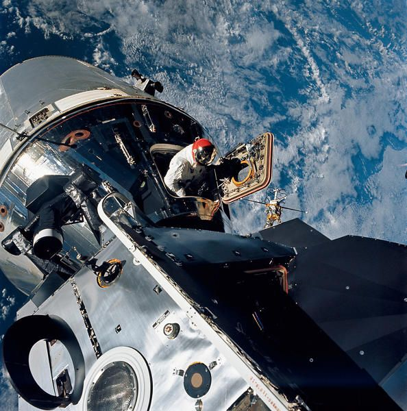 Excellent view of the docked Apollo 9 Command and Service Modules CSM and Lunar Module LM, with Earth in the background, during astronaut David R. Scott's stand-up Extravehicular Activity EVA, on the fourth day of the Apollo 9 Earth-orbital mission. Scott, command module pilot, is standing in the open hatch of the Command Module CM. Film magazine was E,film type was SO-368 Ektachrome with 0.460 - 0.710 micrometers film / filter transmittance response and haze filter,80mm lens.