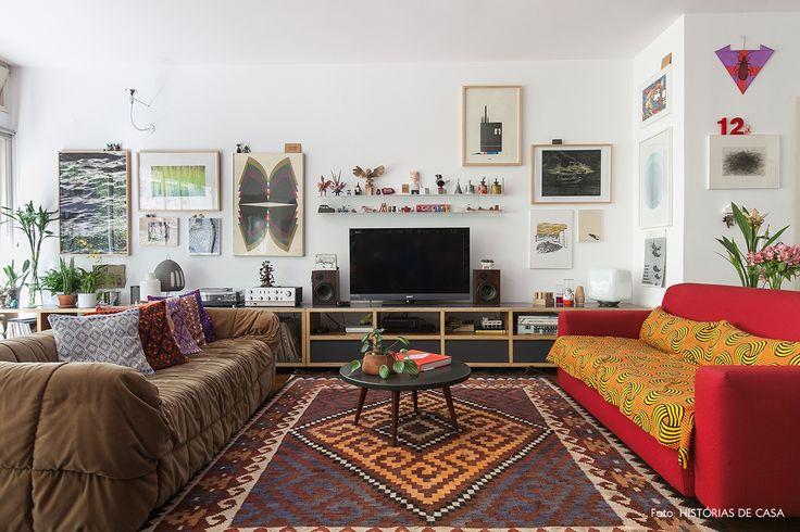 Sala de estar com estilo étnico tem sofá vermelho tecido estampado por cima, tapete kilim e parede galeria.