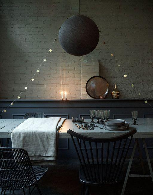 Zo simpel kan versiering zijn: een slinger met grote oud-gouden pailletten vormt een 'tentje' boven tafel en wiegt op de luchtstroom, zodat hij het kaarslicht alle kanten op weerkaatst.