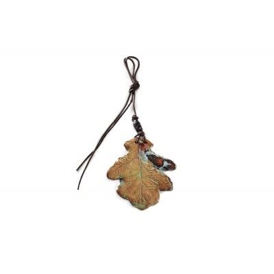 An oak leaf represents strengths and power; it has been made of thin ceramics and glazed both sides. Its unique colours glitter wit a subtle gloss. Comes with a leather strap decorated with a ceramic bead.
