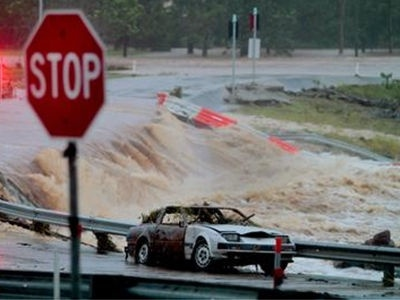 Floodwaters race across the Oxenford - Tamborine road on Australia's Gold Coast on 28 January, 2013.