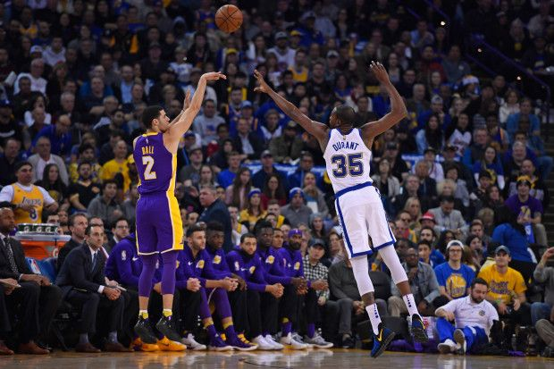 Los Angeles Lakers' Lonzo Ball (2) shoots and scores a three-point basket over Golden State Warriors' Kevin Durant (35) during the first quarter of their NBA game at the Oracle Arena in Oakland, Calif. on Friday, Dec. 22, 2017. (Jose Carlos Fajardo/Bay Area News Group)