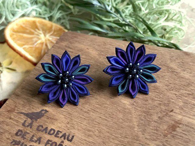 人気のブラックベリーカラーが、イヤリングになりました。 大きめサイズが欲しい!というお客さまからのリクエストにお応えして、直径2.5㎝、しっかり主張してくれるサイズです。 藍色、紺色、紫、深緑、紫紺の花びらを、ほとんど黒に近いダークナイトブルーで縁取っています。 花芯はつやっとしたブラック。ベリーのようで美味しそうです。 洋装にも和装にも合わせられる耳飾りです。 重さはコットンパール程度。 吹けば飛ぶほどの軽さです。 オフィスやデートなどの普段づかいはもちろん、結婚式やパーティーのドレスや浴衣、成人式の着物など長時間着用するシーンでも、とっても楽ちんですよ! 「つまみ細工」は、小さな正方形の生地を、ピンセットを使って一枚一枚ていねいに折りたたみ、糊付けしてつくる、日本の伝統工芸です。 ちいさな花びらやパーツをひとつずつ配置して、手作業でおつくりしています。 繊細な手仕事の一品をお手元にどうぞ。 素材:コットン 金具:クリップタイプのイヤリング(取り外し可能な滑り止め&耳の痛くなりにくいシリコン付き) 寸法:お花の直径約2.5cm ※つける位置に...